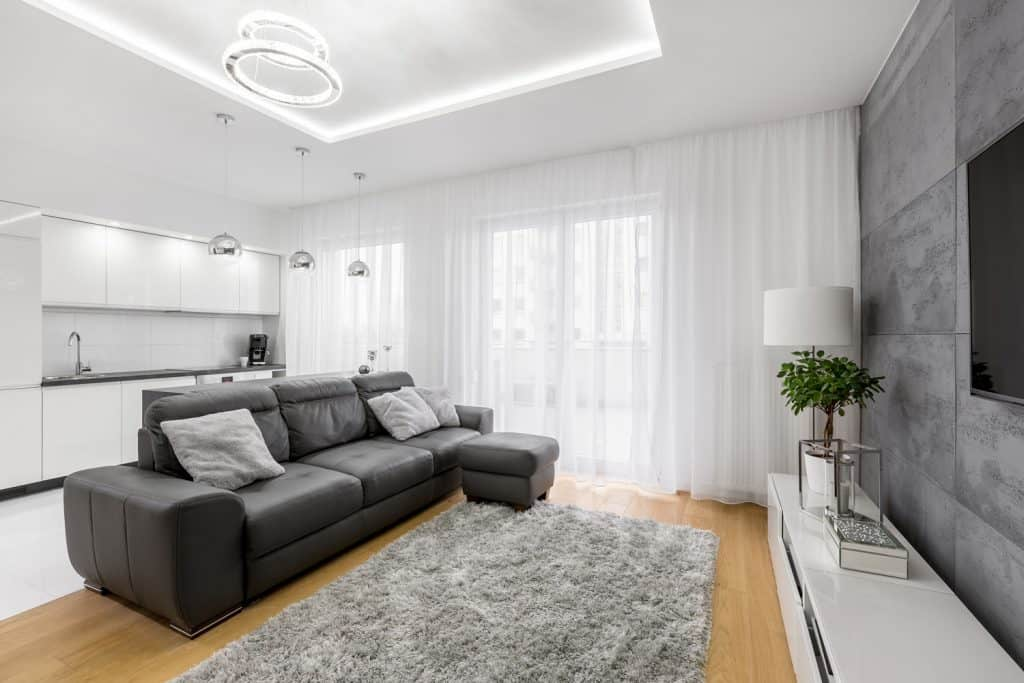 A dark and gray themed living room with white curtains, gray sectional sofa with a gray ottoman and a gray patterned accent wall