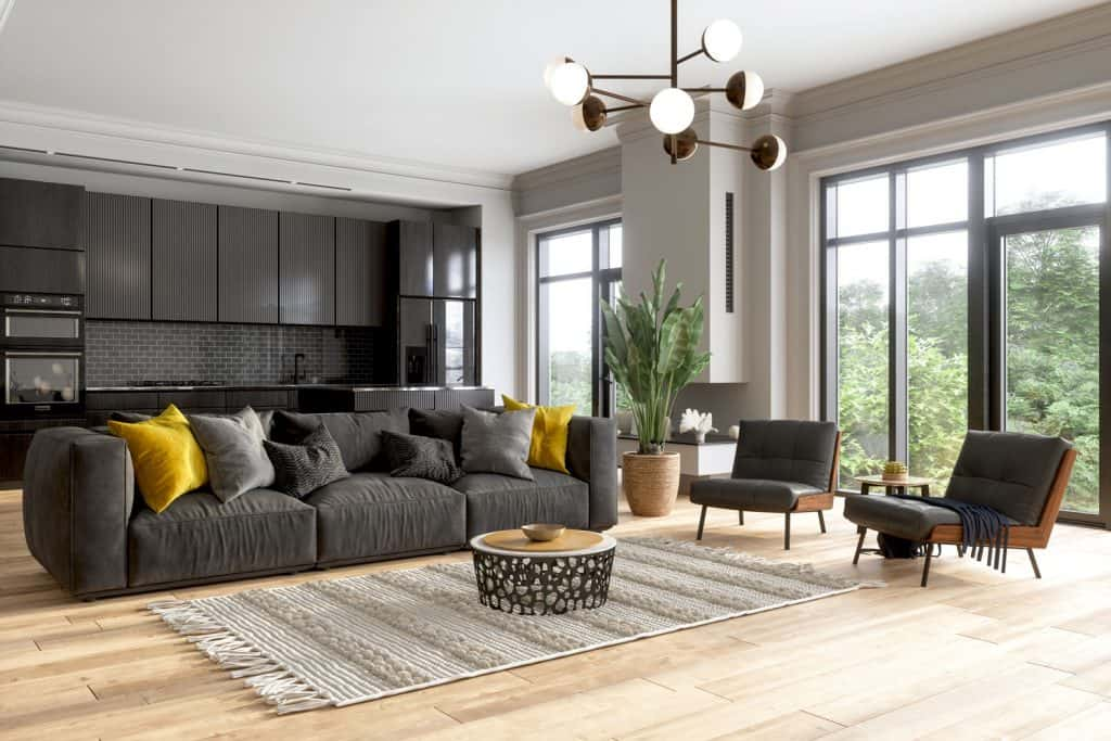 A huge and spacious living room with huge windows, a gray sectional sofa and a modern chandelier
