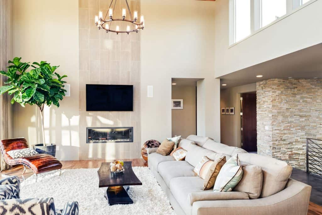 A huge ceiling high living room incorporated with light furniture, beige painted wall and an indoor plant on the side