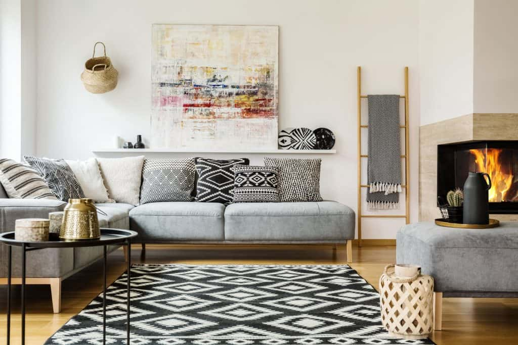 A modern retro inspired living room with cozy colored furniture, gray patterned throw pillows and painting on the wall