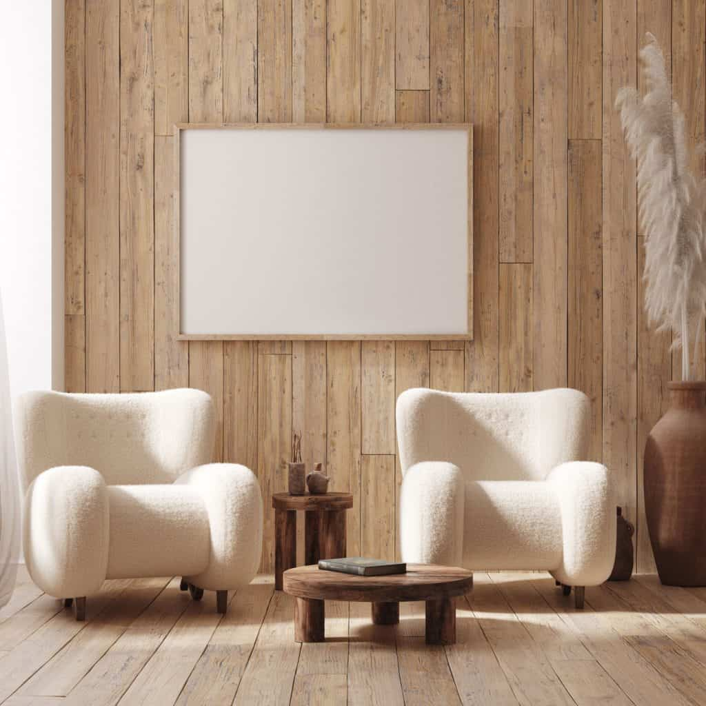 A rustic inspired living room with wooden paneled walls, beige accent chairs, and wooden coffee and end table