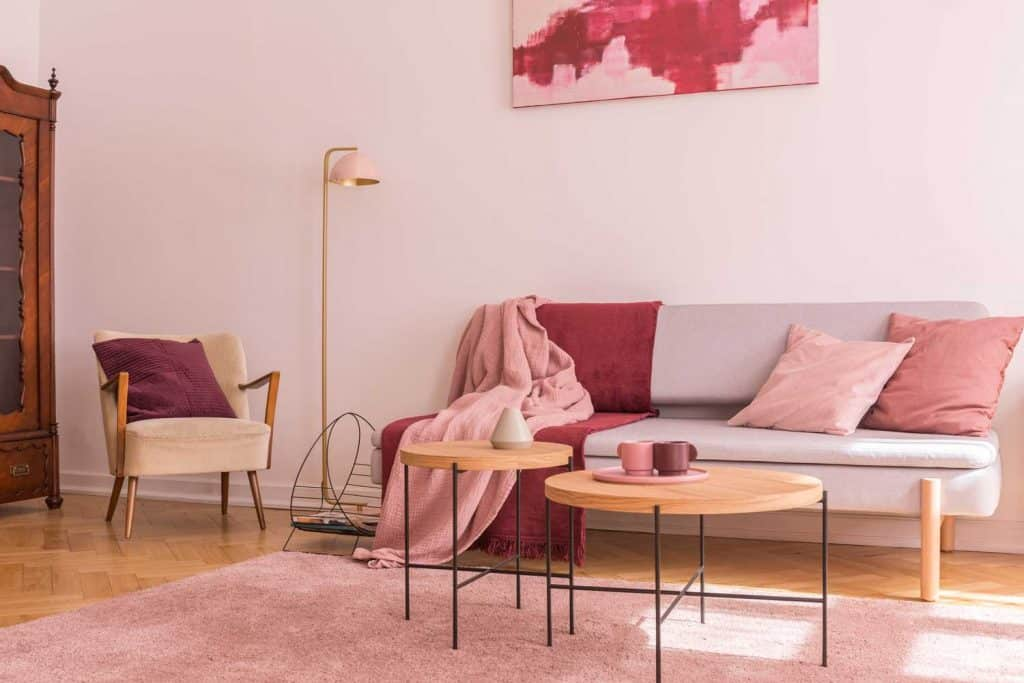 A small and light pink colored living room with pink throw pillows, pink walls and round solid wooden coffee tables