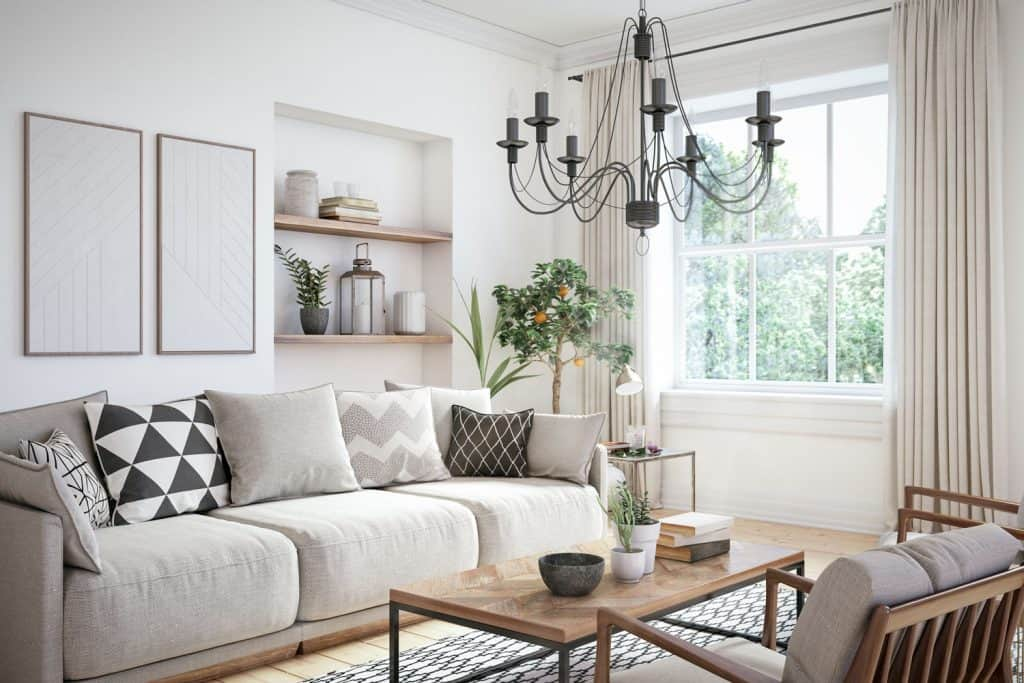 A white Scandinavian inspired living room with light furniture, light patterned throw pillows and a gray candle chandelier