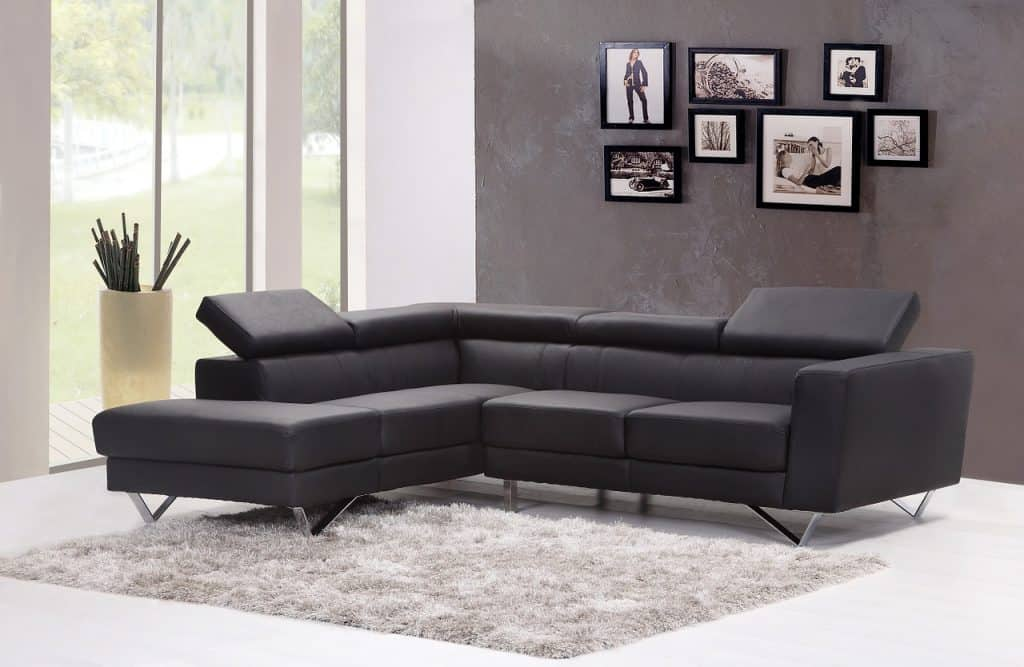 Modern living room interior with pictures on gray wall and dark gray corner sofa