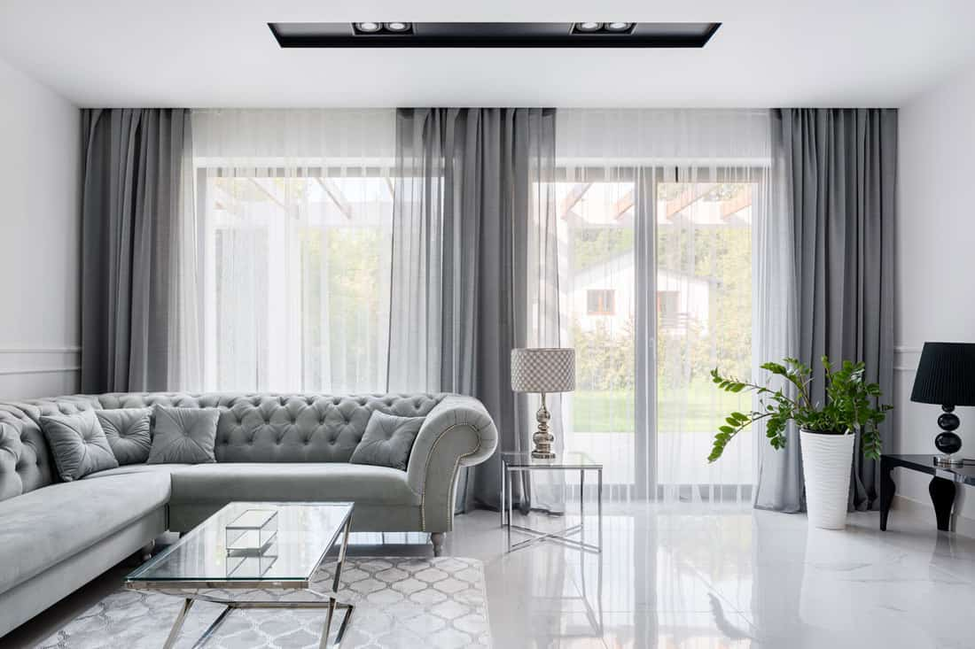 Silver curtains with gray couches with matching white tiled living room