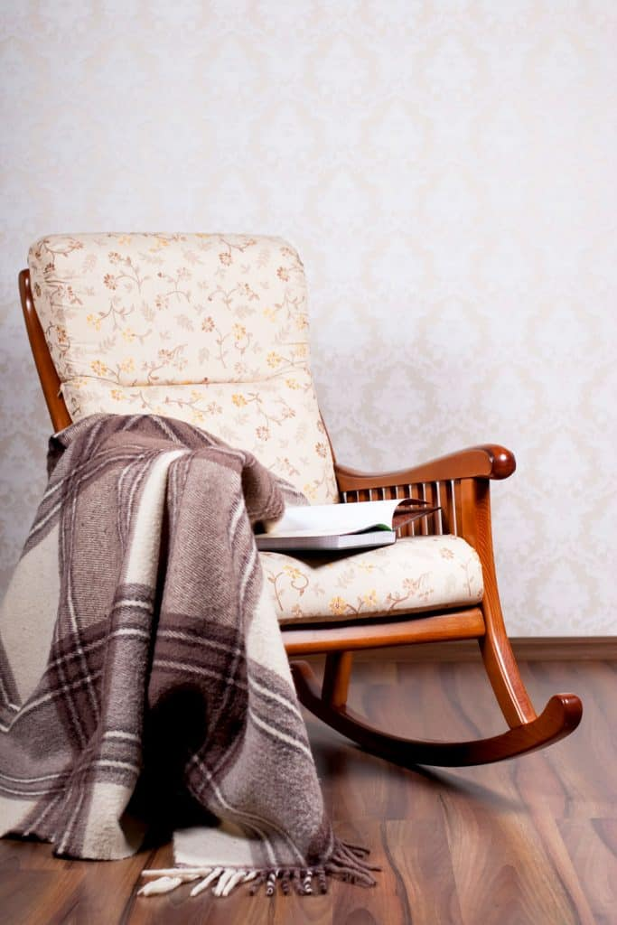A rocking chair with a blanket on the corner of a living room