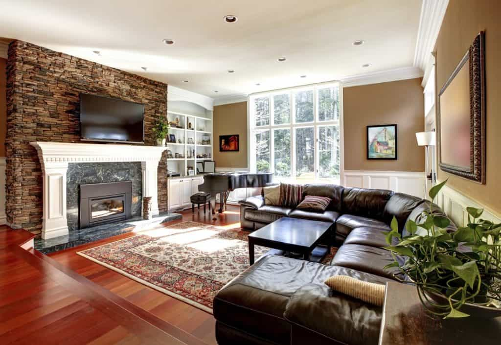 Traditional living room with wood flooring, dark brown leather couch and fireplace