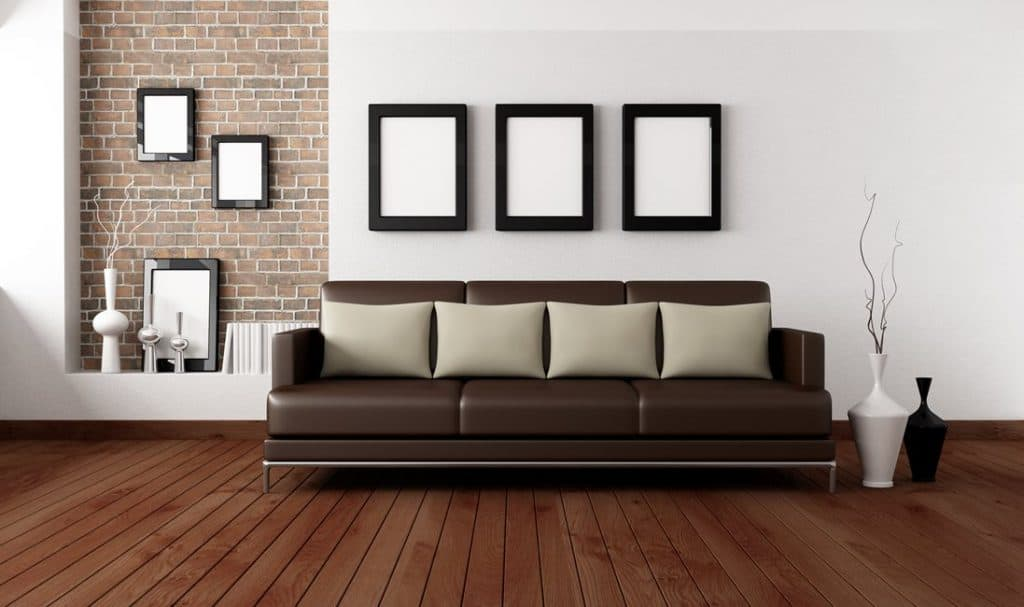 Dark brown couch with light pillows in minimalist living room with parquet floor