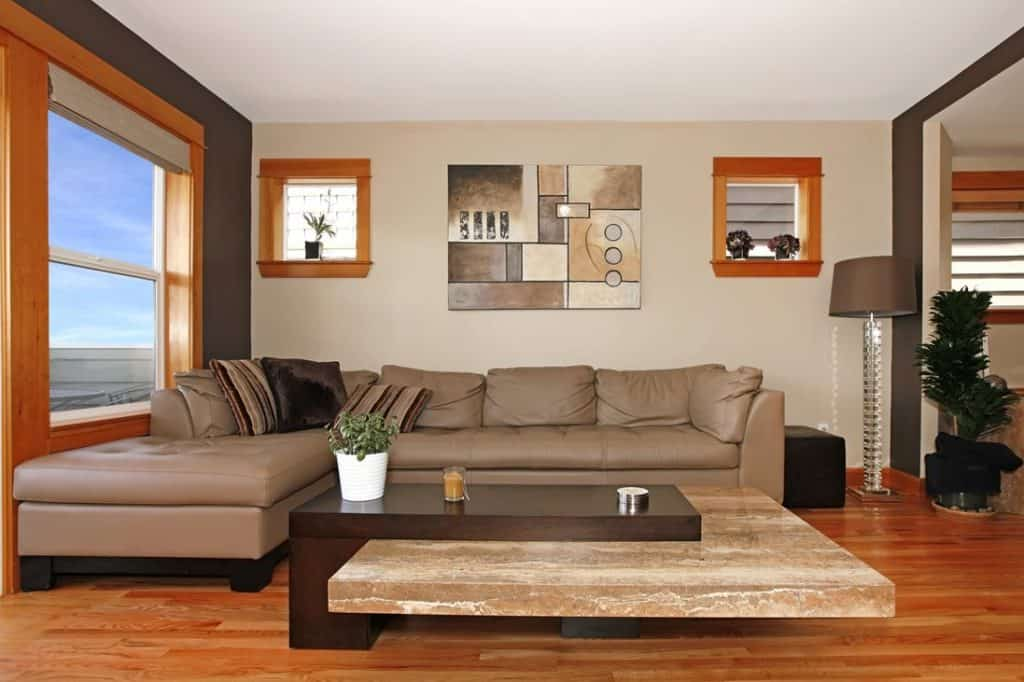 Brown leather couch in a modern living room with throw pillows, art decor on wall and parquet floor