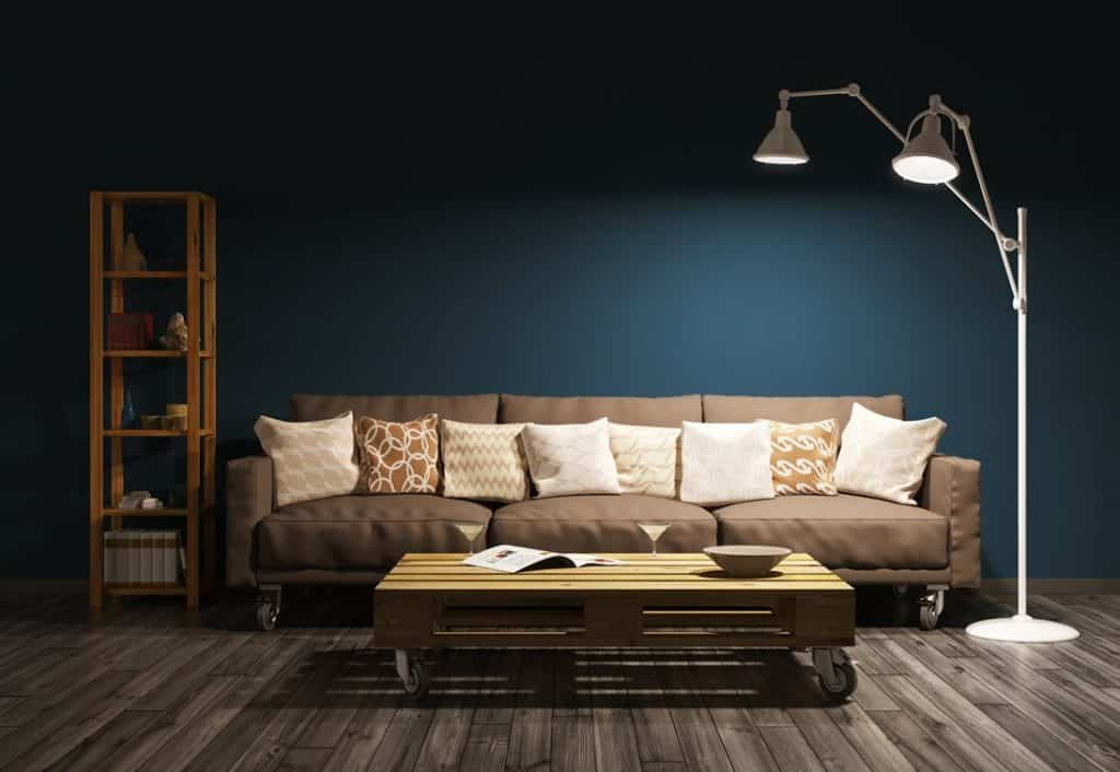 Brown couch in an industrial-style reading corner with a row of light-colored cushions