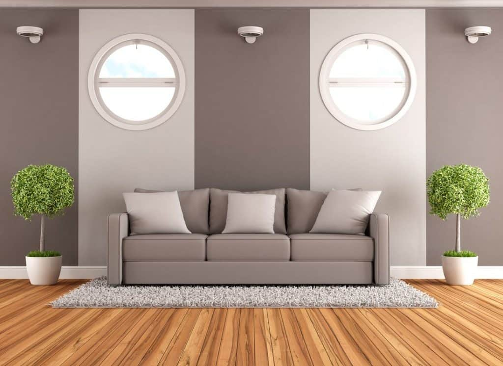 Cozy couch with throw pillows in minimalist living room with parquet floor and house plants