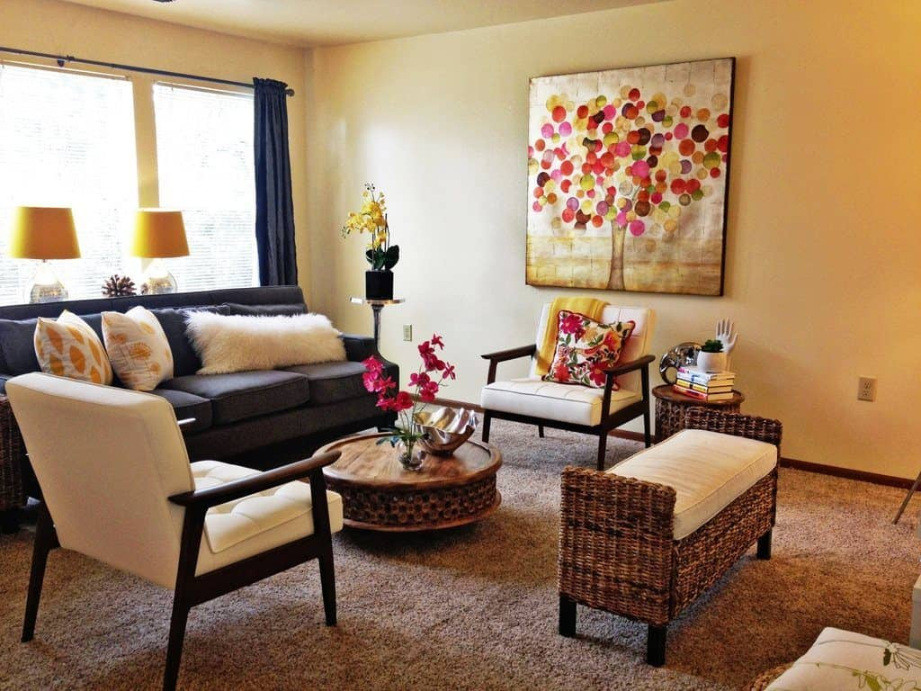 Shabby-chic living room with art decor on wall, dark brown sofa and floral throw pillows