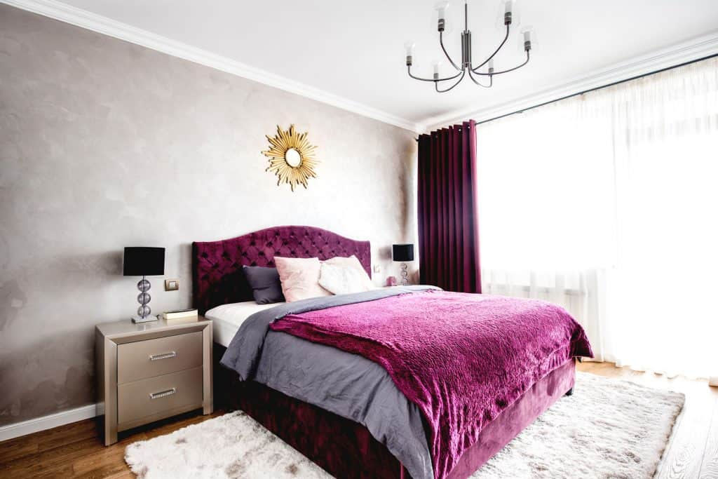 A bright and luxurious bedroom with purple and gray beddings