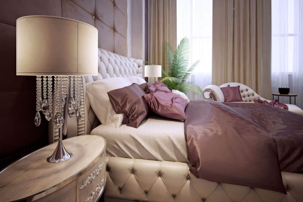 A cozy and warm bedroom with beige colored bed and curtains mixed with purple blanket and pillows