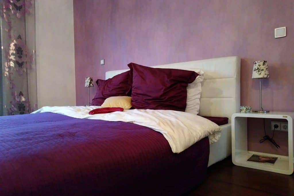 A gorgeous king sized bed with a purple and white pillows and a decorative header area