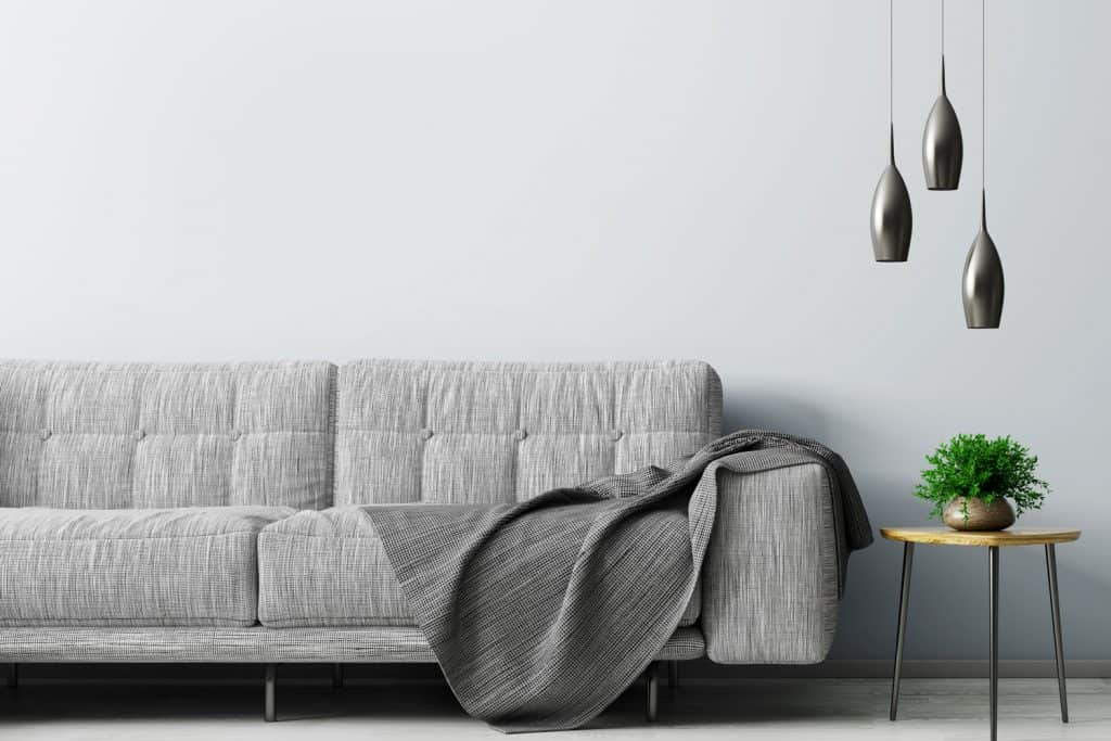 A gray sofa with a gray drape with dangling lamps pointed to the end table