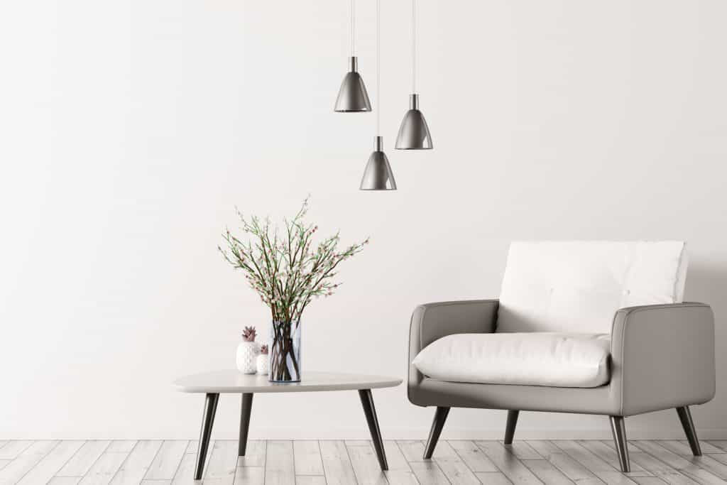 A light silver sofa with an end table in front with an indoor plant on top and silver dangling lamps