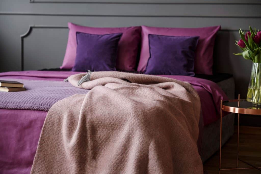 A modern bedroom with purple beddings, pillows, and a brown drape on the bed