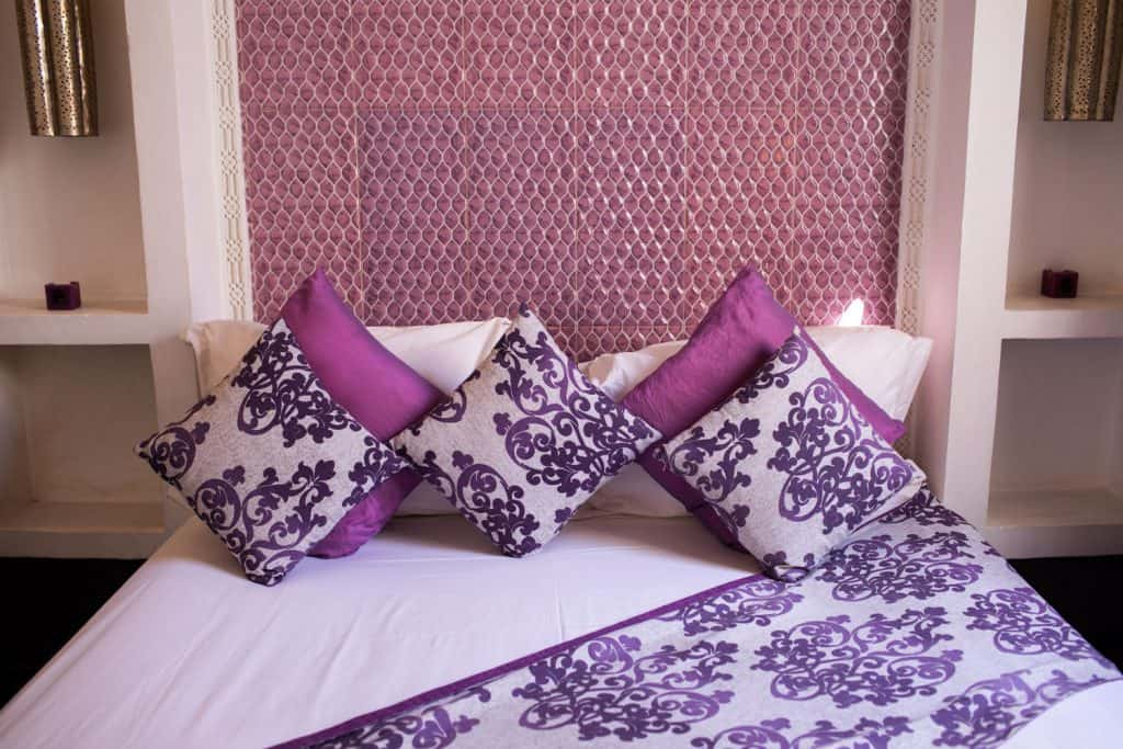 A purple themed bedding with floral blankets, floral throw pillows, and a purple foam header