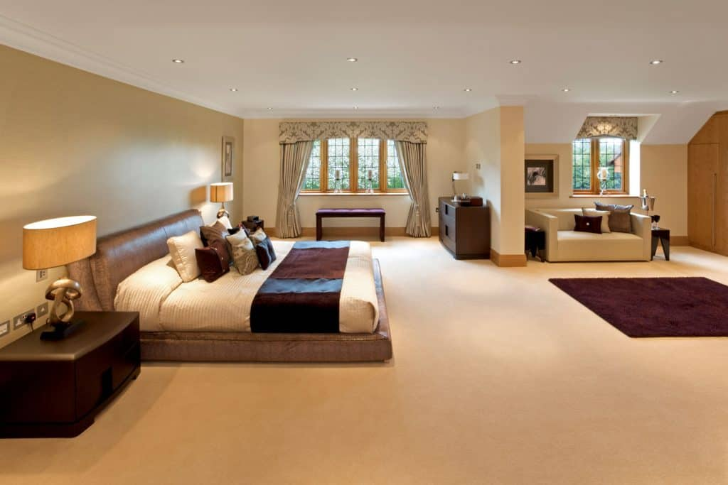A spacious and elegant light cream colored flooring and walls with a violet throw pillows and violet blankets