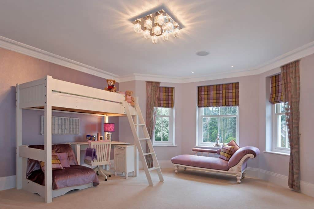 A spacious bedroom with a double decker bed with white walls and a a white painted bay window