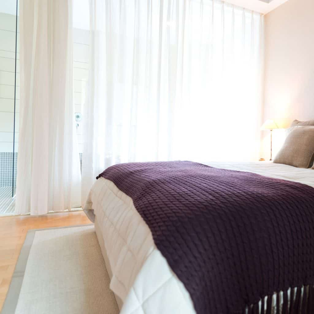 A white and purple bedroom with purple and white beddings