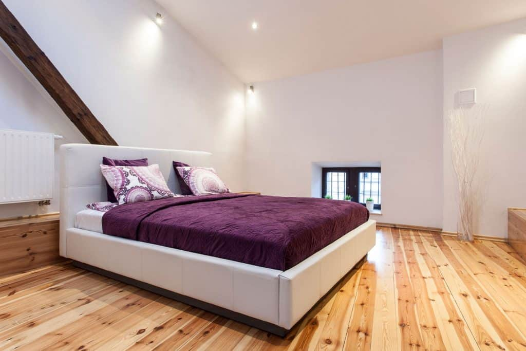 A white and rustic themed bedroom with wooden flooring and purple beddings
