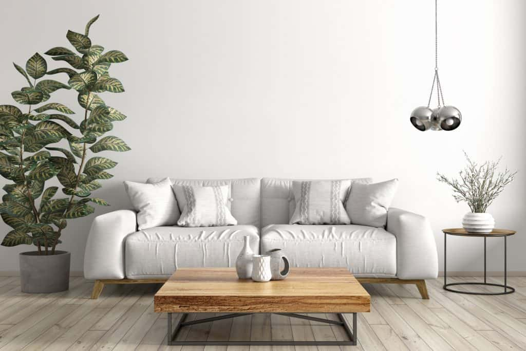 A white sleeper sofa inside a dark gray themed living room with a wooden coffee table, wooden flooring, and a silver dangling lamp