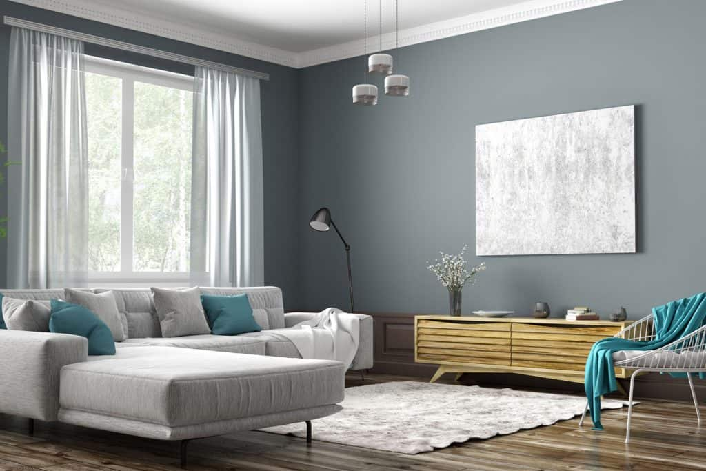 Interior of a contemporary living room with a light silver sofa, dark gray painted wall, and a gray carpet on the flooring