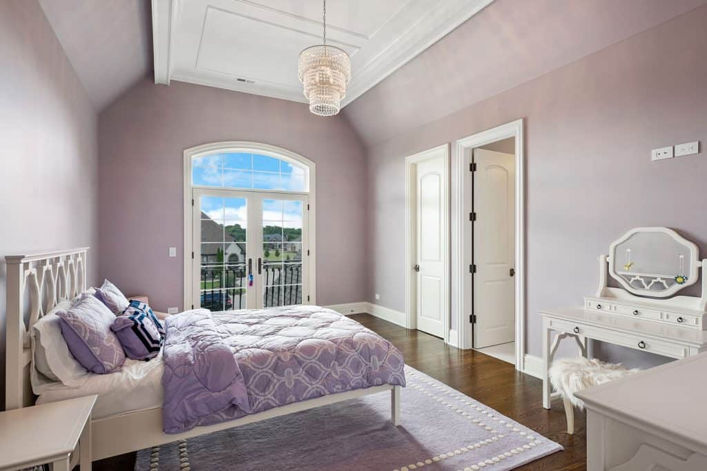 Interior of a gorgeous purple themed bedroom with floral beddings, purple area rug, and a hardwood flooring