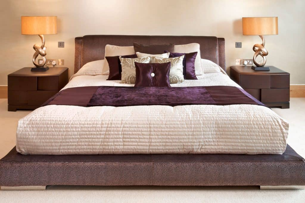 Interior of a low king sized bedroom with purple beddings, beige painted walls, and orange side lamps on end tables