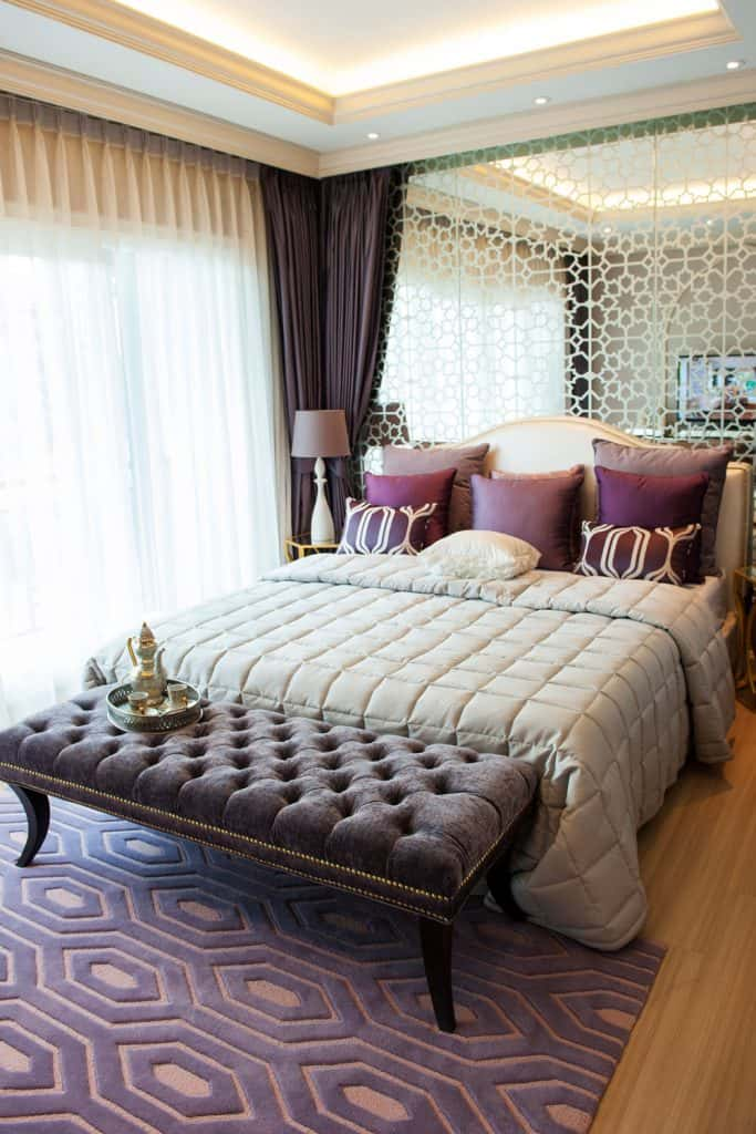 Interior of a modern bedroom with cozy and expensive purple beddings and a patterned area rug