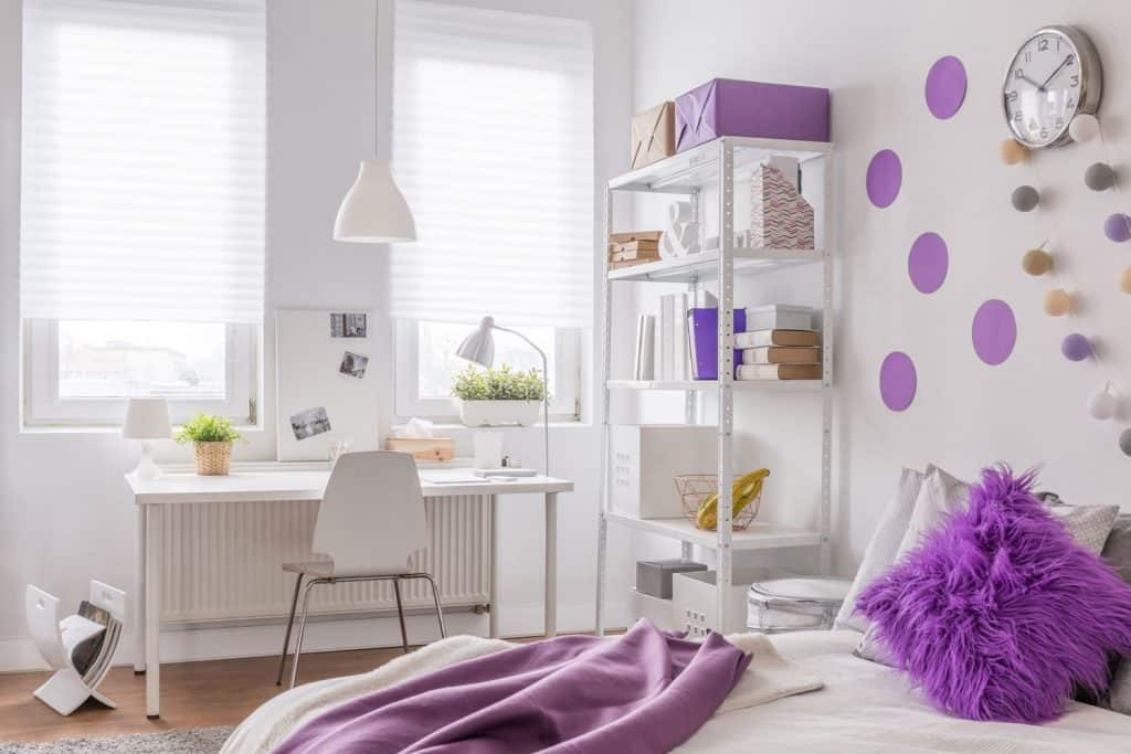 Interior of a white and purple themed bedroom with white walls, white furniture's and desk tables, and a bed with a fur like throw pillow