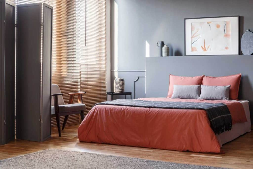 A gray inspired living room with gray painted walls, red beddings, and brown blinds on the window