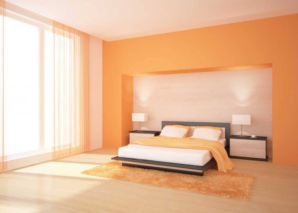 Spacious and luxurious interior of a modern bedroom with white and orange beddings