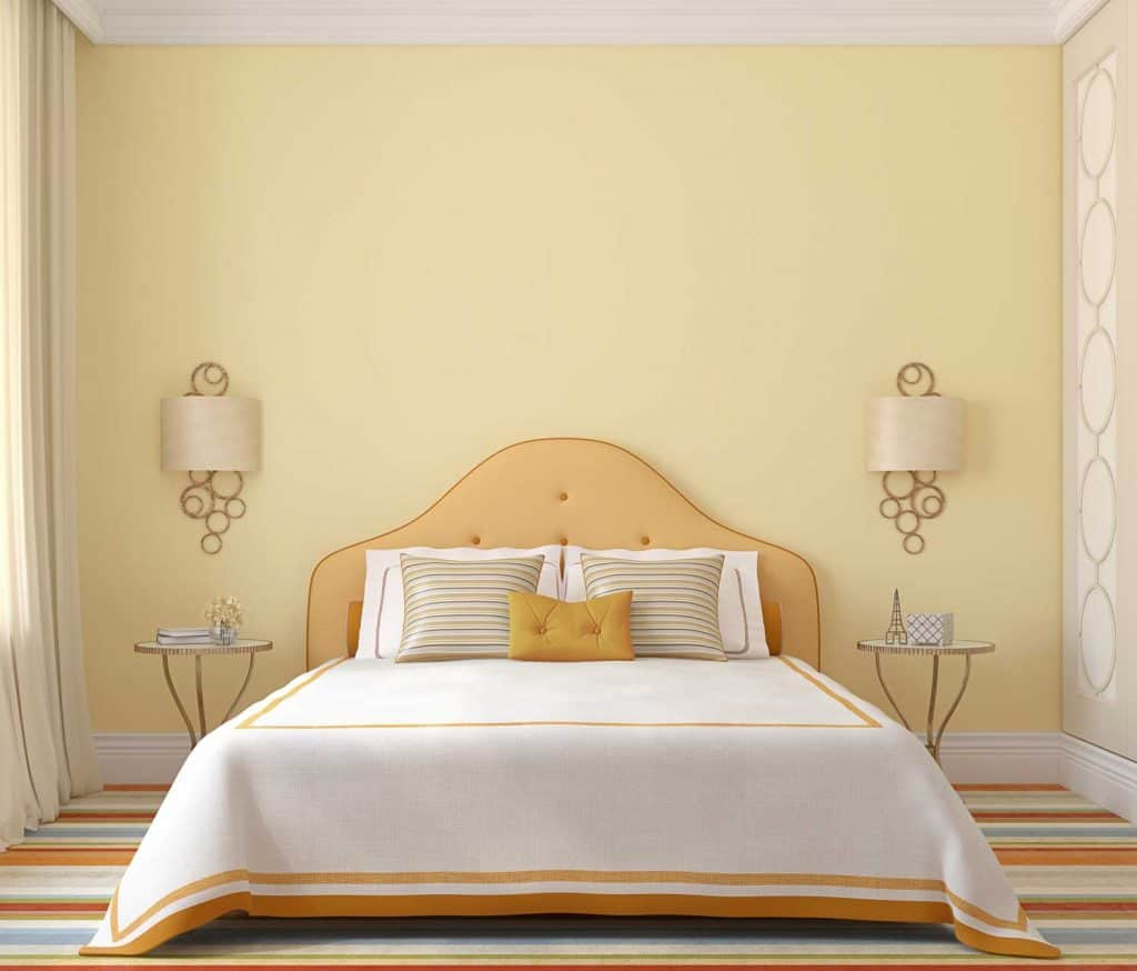 A pastel themed bedroom with white beddings, round metal framed end tables, and a beige curtain
