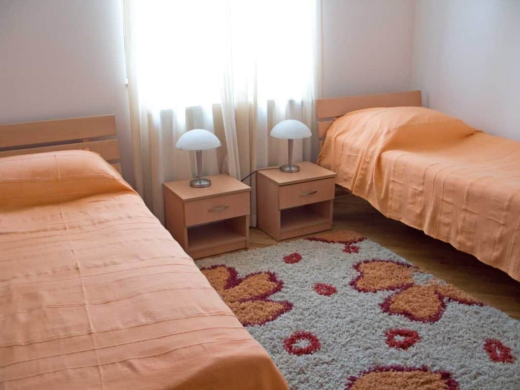 A small two bedroom with orange nightstands and orange beddings