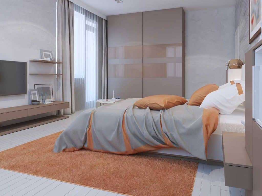 Ultra modern bedroom with with modern furniture's, gray and orange beddings, and white painted walls
