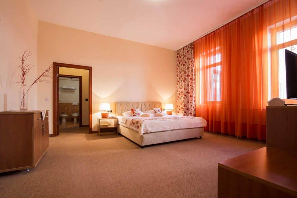 Spacious and luxurious bedroom with carpeted flooring, white beddings, and lamps on the side