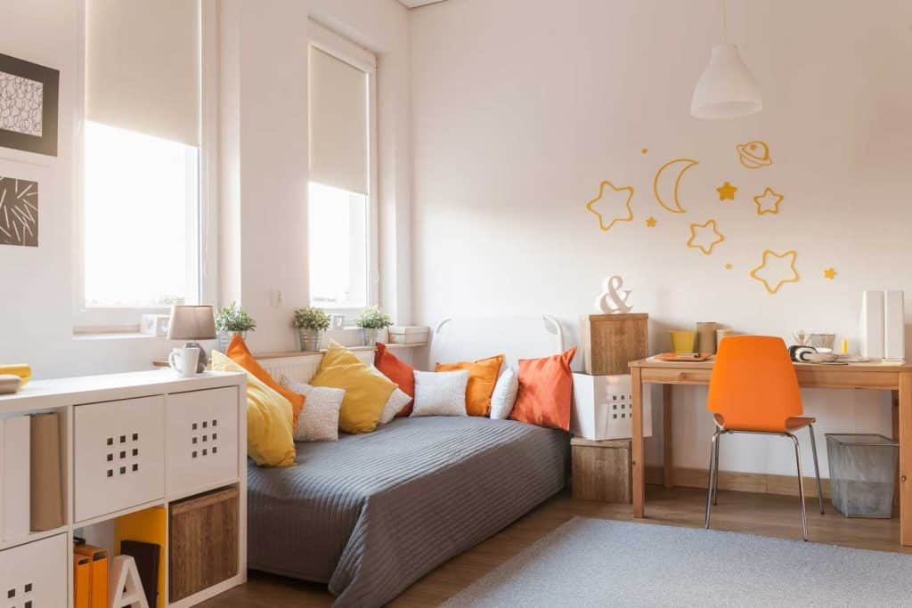 White modern interior of a bedroom with a gray bed with orange and white throw pillows
