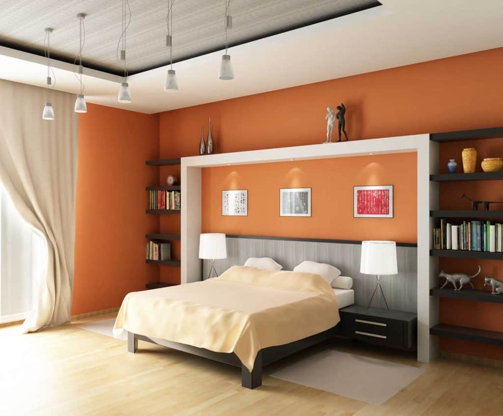 Luxurious and modern interior of a living room with orange painted walls with beige and white beddings