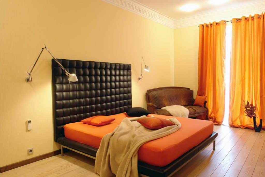 Cream colored walls, huge black bed with a huge header, orange bed with orange pillows, and wooden flooring