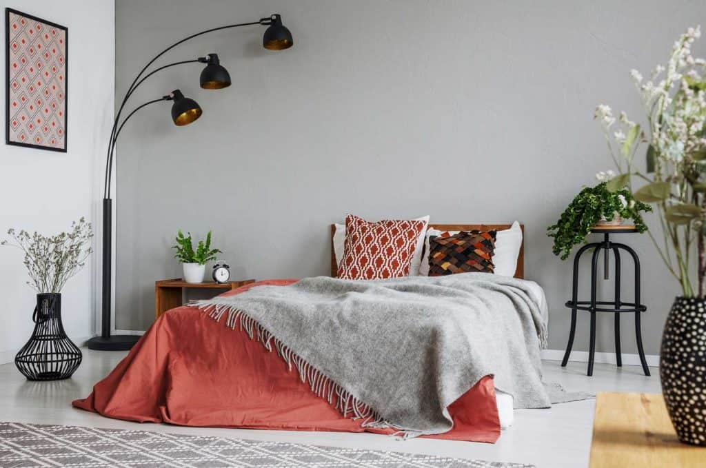 Interior of an ultra modern bedroom with gray painted walls, dangling floor lamps, and red and gray beddings