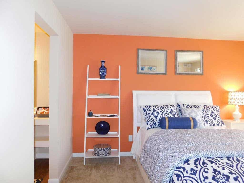 A huge blue floral bed with floral pillows and an orange accent wall