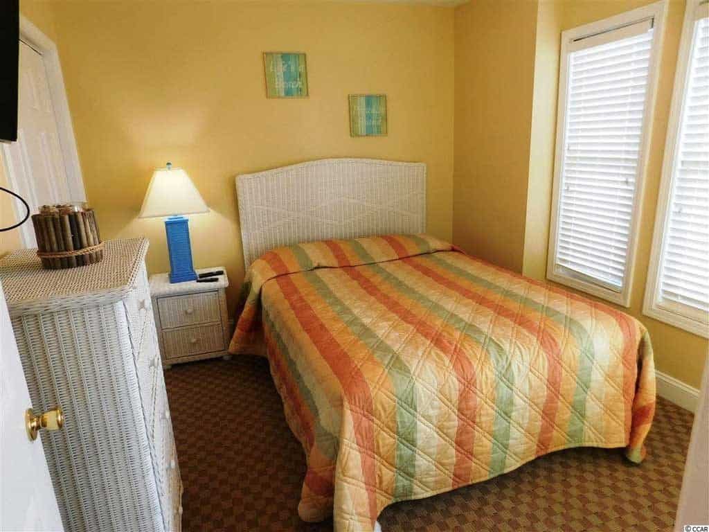 A small orange walled bedroom with bright colored striped blankets