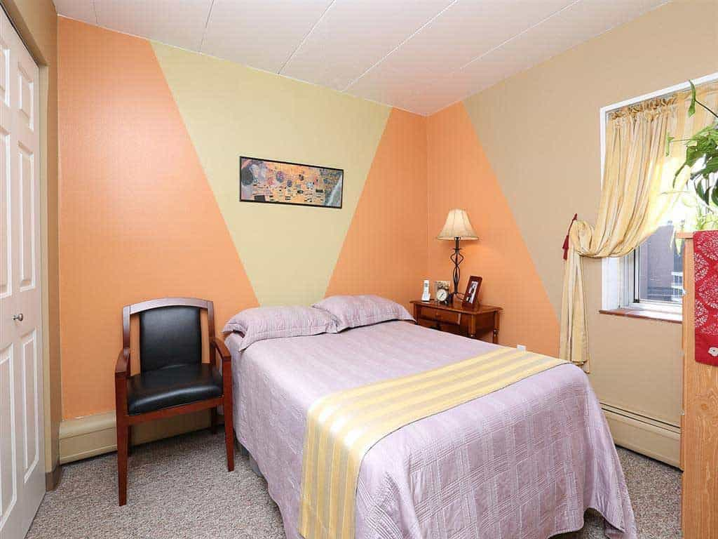Modern interior of a bedroom with purple beddings and a small wooden chair on the side