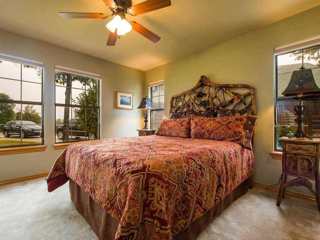 A huge king sized bed with floral beddings, orange walls, and a ceiling fan