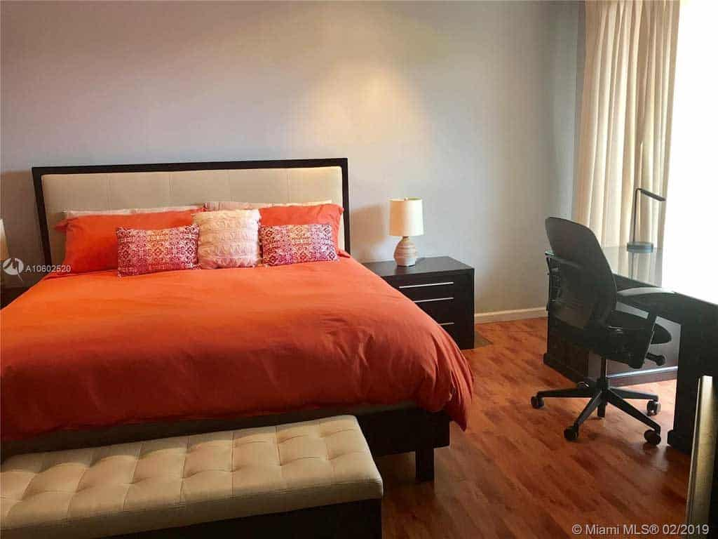 A huge orange bed with throw pillows, wooden laminated flooring, and a small work desk on the side