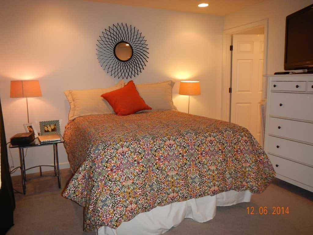 A floral bed with carpeted flooring, and white painted walls, and lamps on the side