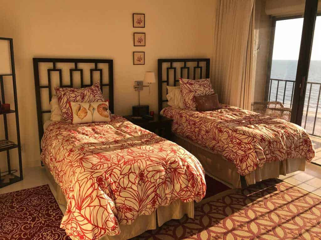 A two bedroom floral beddings, metal bed, and cream painted walls